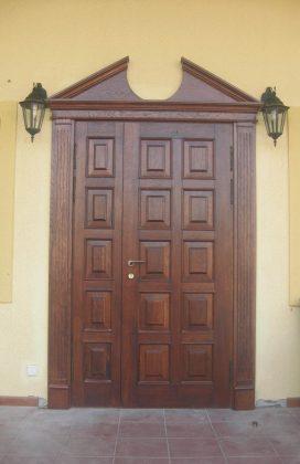 Однопольная филенчатая входная дверь с карнизом, наличниками