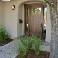Входная дверь в широком проеме с глухими окнами
