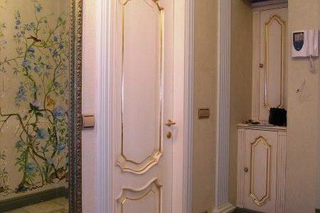 Белая входная дверь из массива дуба с золотой патиной.
